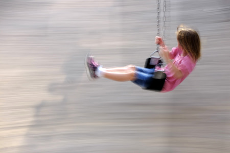 giggling: Little girl playing on swing set at a park