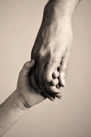 성인 또는 부모가 작은 아이의 손을 잡고