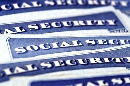 social security: Closeup detail of several Social Security Cards representing finances and retirement