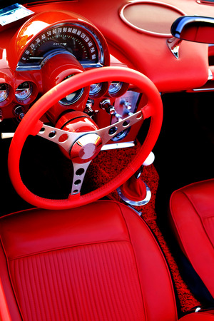car show: Detail of interior red sports car steering wheel speedometer