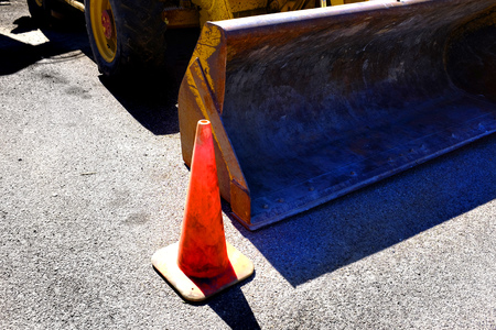 tractor warning sign: Orange cone and heavy equipment bulldozer dozer for street repair and constructions Stock Photo
