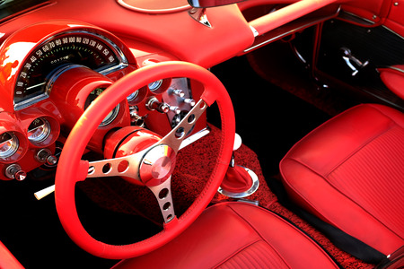 vintage power: Detail of interior red sports car steering wheel speedometer