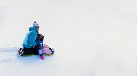 Kids sledding down snowy hill on sled fast speed Stock Photo