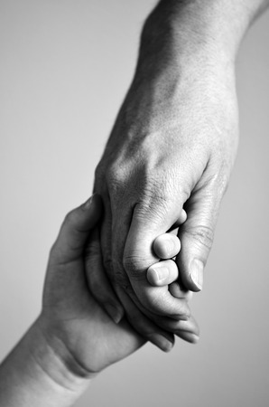 adult hand: Adult or parent holding the hand of a small child