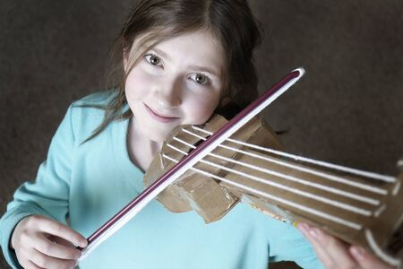 beautiful teen girl: Young girl playing toy violin smiling happy