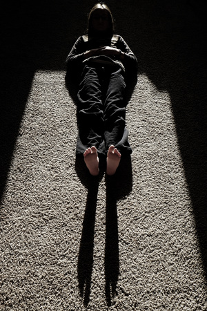 causing: Sunlight causing shadow of person lying on floor feet legs head