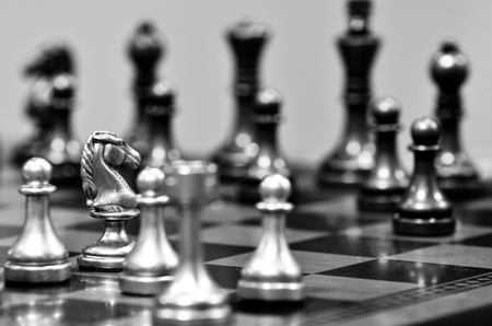 chess board: Chess board with white knight facing opponent in match