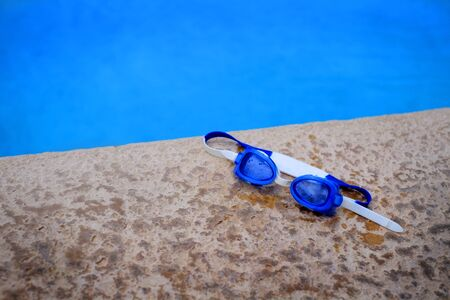 swim goggles: Detail of blue swim goggles  for summer next to swimming pool