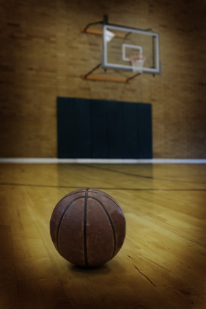 swish: Basketball on floor of empty basketball court Stock Photo