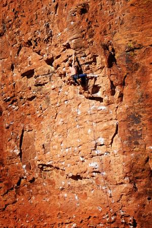 succeeding: Single girl climbing along rocky ridge on a trail
