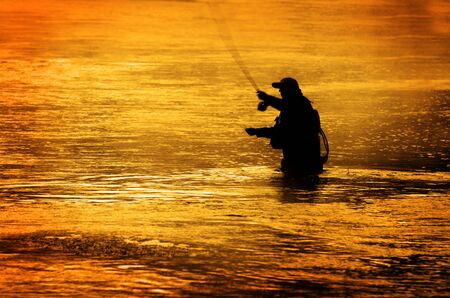 a hobby: Man fishing in river or lake silhouette by sunrise and misty water Stock Photo