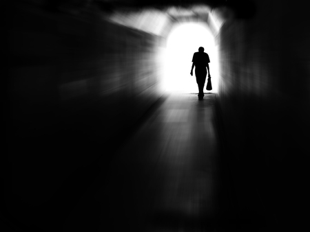 Long tunnel walkway with person at the end in motion