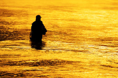 flyfishing: Man fishing in river or lake silhouette by sunrise and misty water Stock Photo