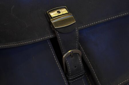 to clasp: Metal clasp on old leather case with stitching