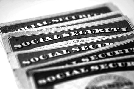 financial official: Closeup detail of several Social Security Cards representing finances and retirement