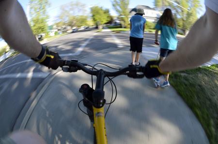 sidewalk: Riding Bike Fisheye View pov biking in park with kids Stock Photo