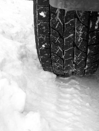 tire tread: Old Truck Tire in Fresh Snow Rugged Tread Stock Photo