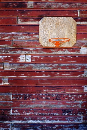 Old basketball hoop on weathered old red barn wall