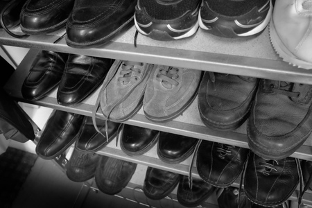 Row of Old Shoes on Shelves with Laces Black and White Archivio Fotografico