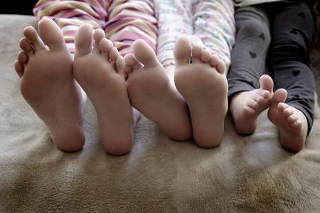 Feet of kids in pajama pants hole legs toes