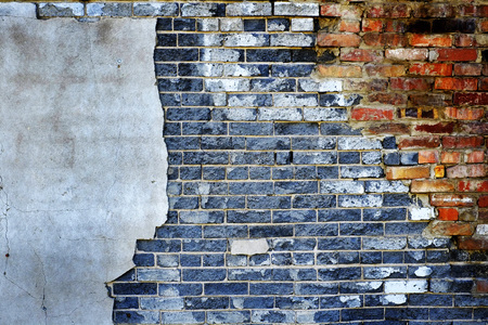 Gray and red bricks on plastered wall that is falling apart Stock Photo