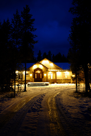 Cabin in stand of pine trees covered in snow in the winter in the evening with blue sky Stock Photo