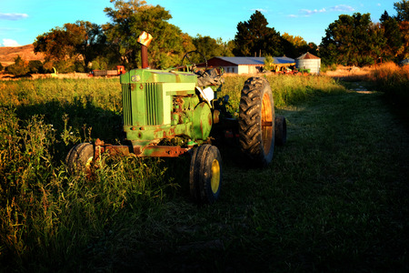 industrialized country: Old Tractor In Field on farm summer day Stock Photo