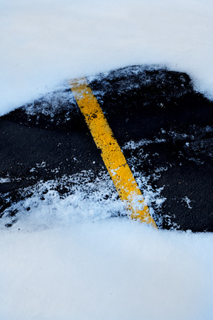 sidelit: Road roadway with snow and ice car tracks slippery