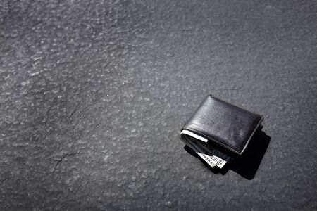 inattention: Lost wallet lying on street or roadway road path with cash Stock Photo