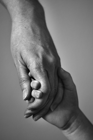 Adult holding the hand of a child showing support and love