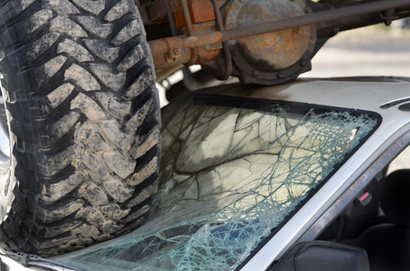 airbag: Car wreck with truck tires on windshield of small destruction crash