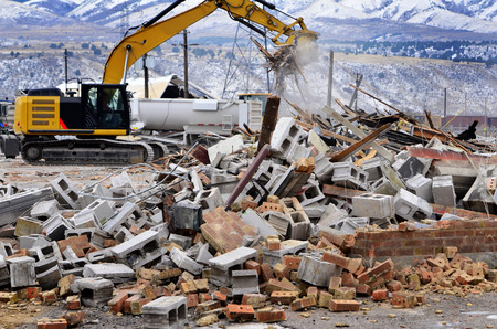 raze: Heavy equipment being used to tear tearing down building construction