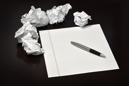 paperball: Pen and paper on a desk with discarded trashed ideas written ouit Stock Photo