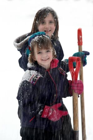 Kids playing in snow with snowflakes falling
