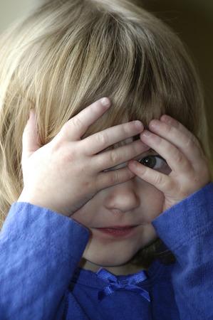 Little girl playing peekaboo peek-a-boo game Stock Photo