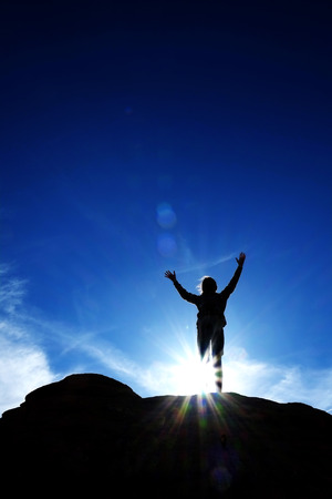 sunlight sky: Single person triumphantly reaching peak summit of mountain with sky and sunlight silhouette