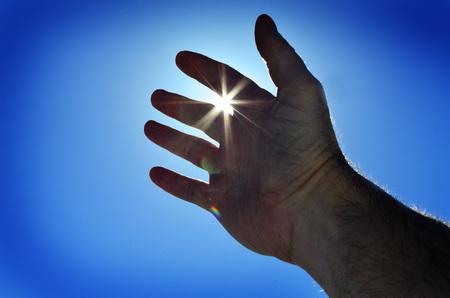 Reaching hand to heaven seeking heavenly light