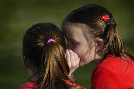 Sisters telling secrets friends by whispering in ears to each other photo