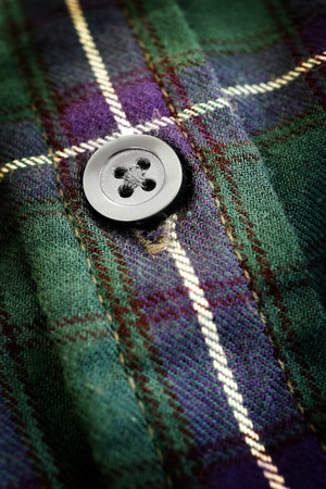 Closeup of button on plaid flannel shirt Stock Photo