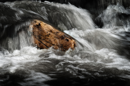 rushing water: Water in a stream or creek flowing over rocks smooth motion