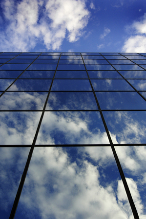 sky reflection: Detail of glass building for business reflection blue sky and clouds