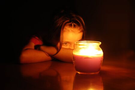 Portrait of little girl at night staring at lit glowing candle photo