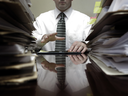 Businessman at desk with piles of files, papers and a notebook pen photo