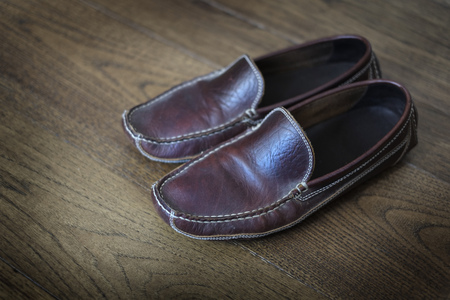 houseshoe: Detail of comfortable leather slipper on polished wooden floor