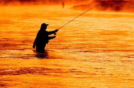 Man flyfishing in misty river in the morning light