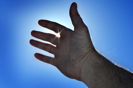 Raggiungere la mano al cielo per cercare la luce celeste