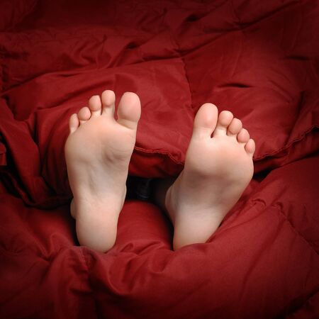 luxury house: Feet in bed with red blanket people resting Stock Photo
