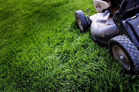 Old lawn mower on lush green grass mowing Stock Photo
