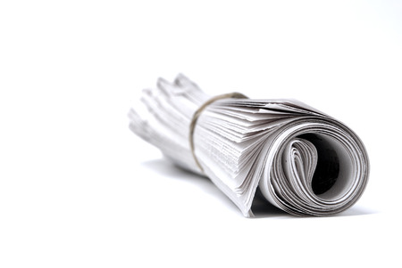 Newspaper rolled up isolated on white for news stories and information Stock Photo