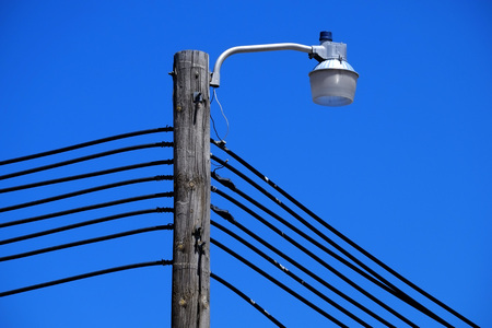 Light pole with power lines and blue sky